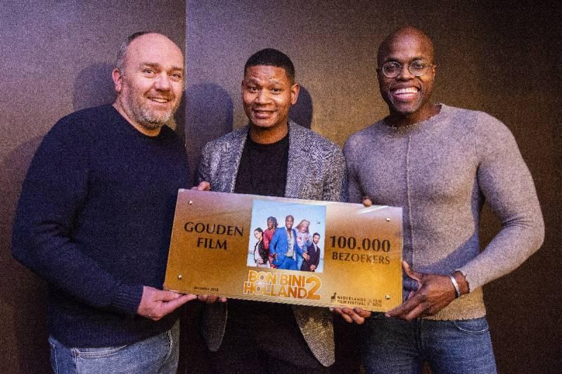 Producent Maarten Swart en acteur Sergio IJssel geven de Gouden Film voor Bon Bini Holland 2 aan hoofdrolspeler en scenarioschrijver Jandino Asporaat (C) Grasshopperstudios / Joke Schut