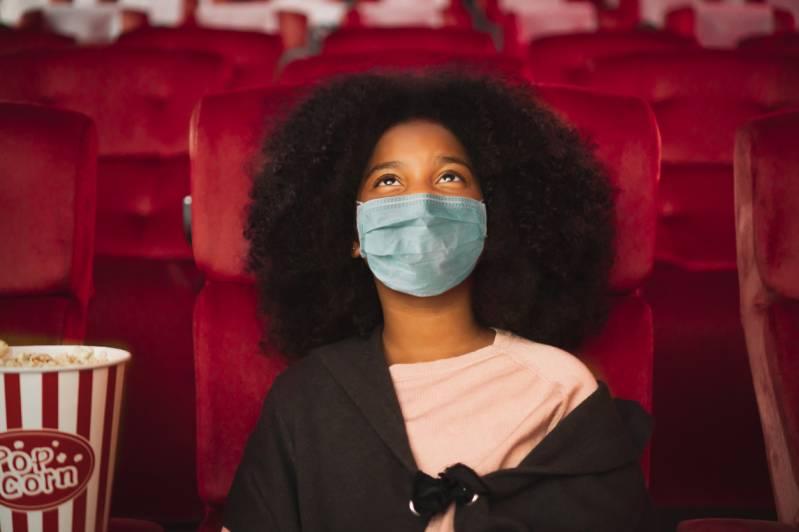 Blij kind met beschermend gezichtsmasker en iedereen op gepaste afstand in verband met civid-19 © 2020 Nattakorn Maneerat